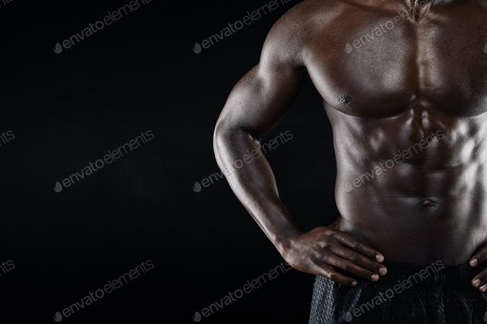 Close-up of shirtless african man with hands on hip