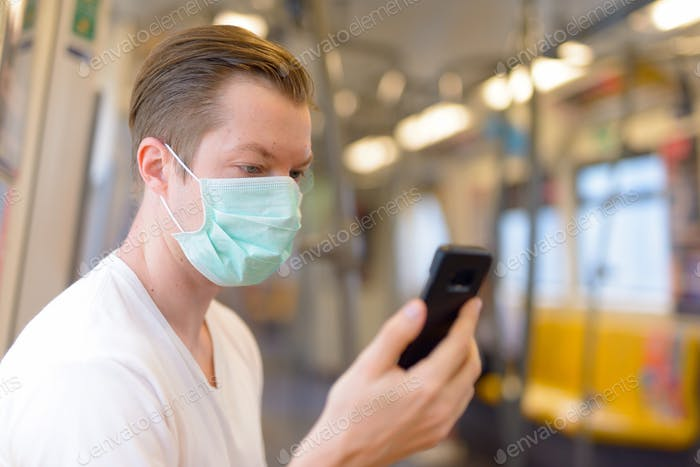 Young man using phone and wearing mask for protection from corona virus outbreak inside the train
