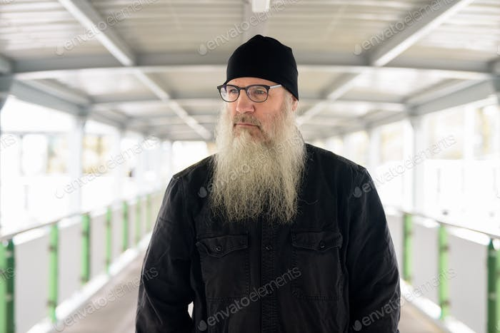 Mature bearded man with eyeglasses thinking at footbridge in the city