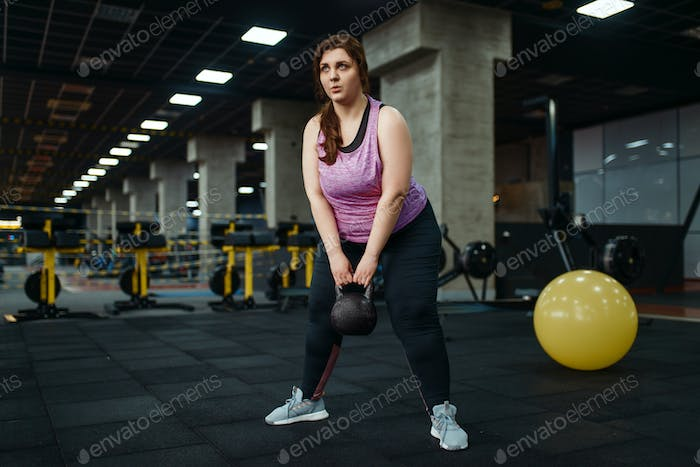 Overweight woman, exercise with kettlebell in gym