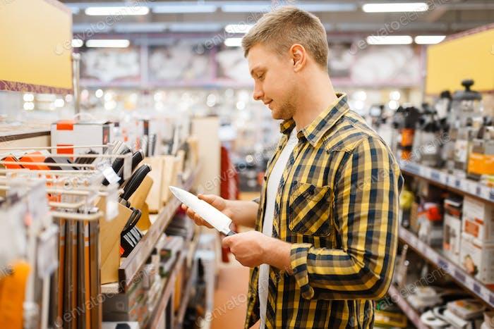 Young man choosing kitchen knife, houseware store