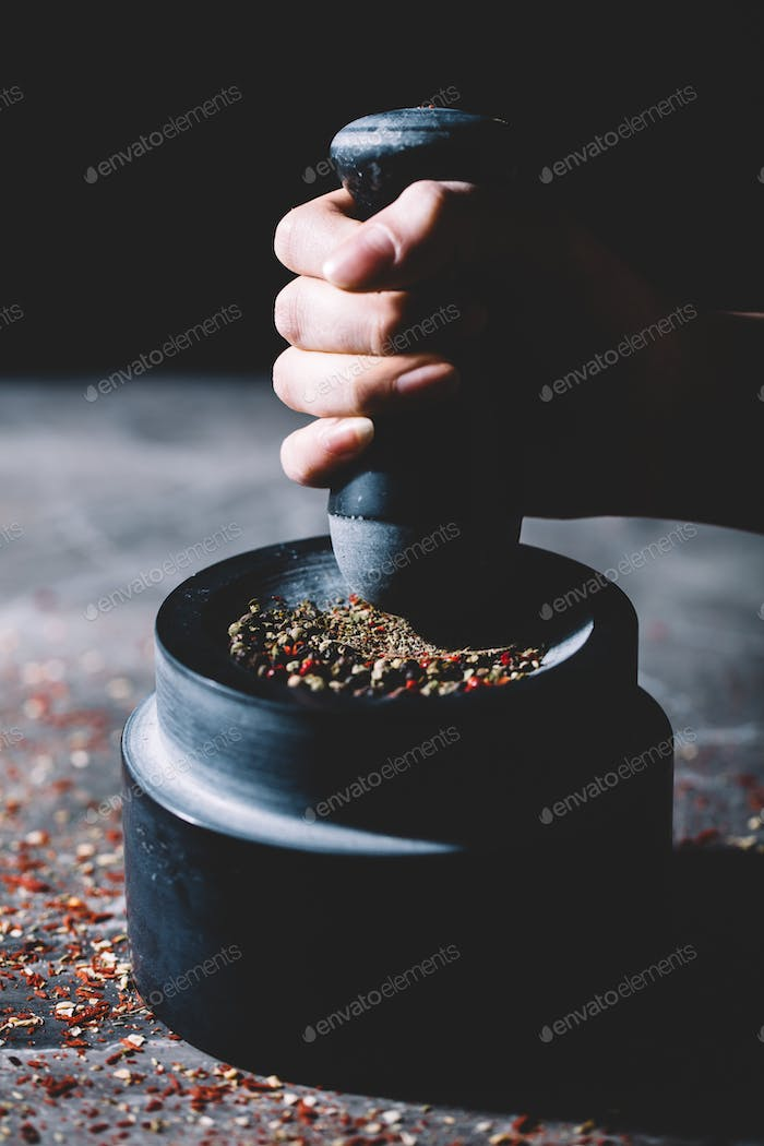 Woman's hand crushing grains of pepper in a mortar