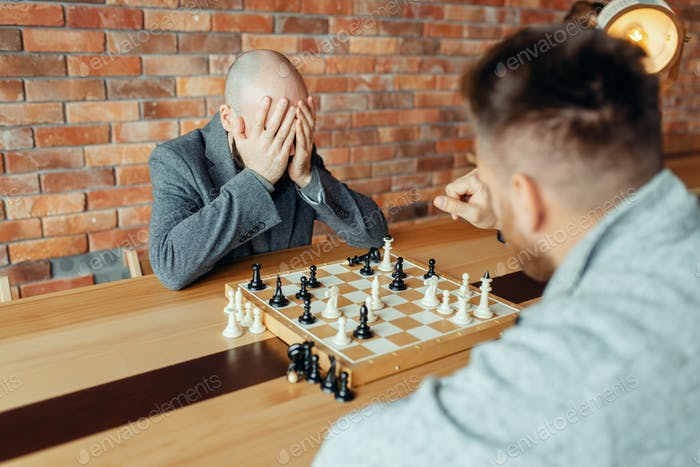 Male chess players playing, white wins, mate