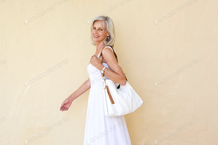 happy older woman in summer dress walking with purse