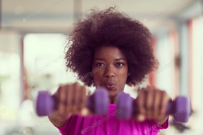 woman working out in a crossfit gym with dumbbells