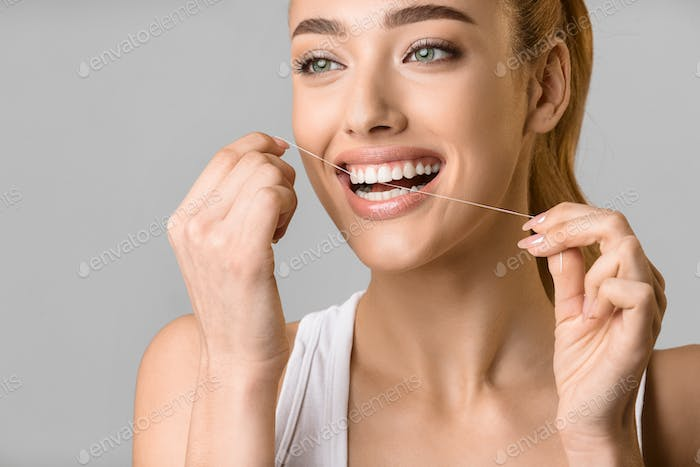 Tooth care. Young woman using dental floss