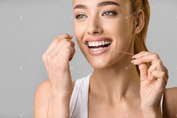 Zahnpflege. Junge Frau mit Zahnseide