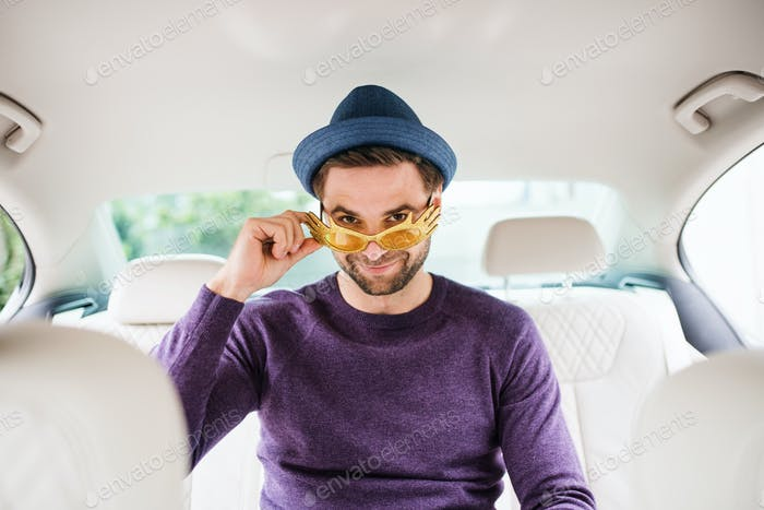 Cheerful man with party accessories sitting in car, having fun