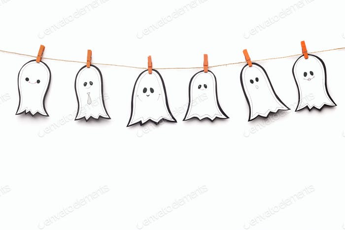 Composition of white ghosts drying on Halloween rope