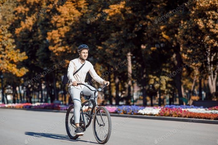 Städtischer Ökoverkehr. Schöner Hipster im Helm genießen Fahrrad