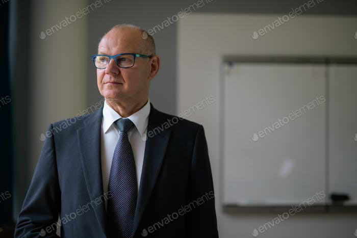 Senior Businessman Thinking By The Window At Work