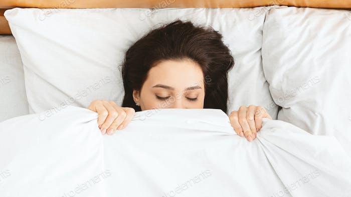 Millennial girl hiding under blanket in bed, panorama