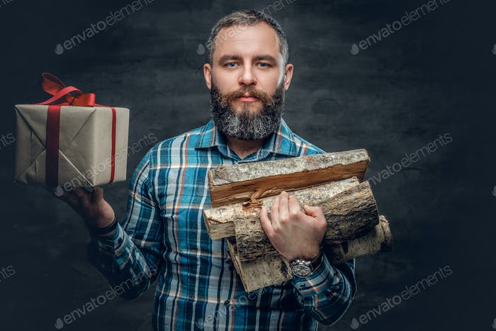 Middle age male holds fire woods and Christmas gift box.