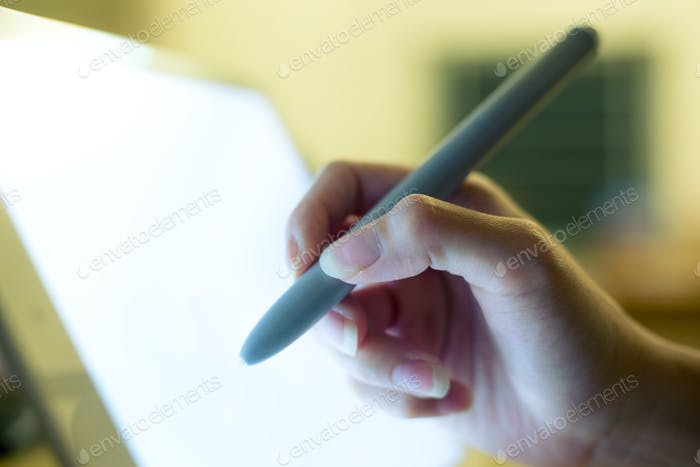 Hand holding a pen touching screen on modern digital tablet