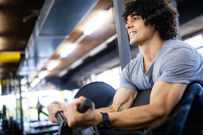Young attractive adult man exercising and doing weight lifting at gym