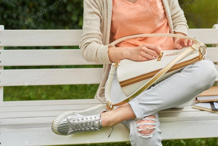 Girl sits on wooden benck with a white bag