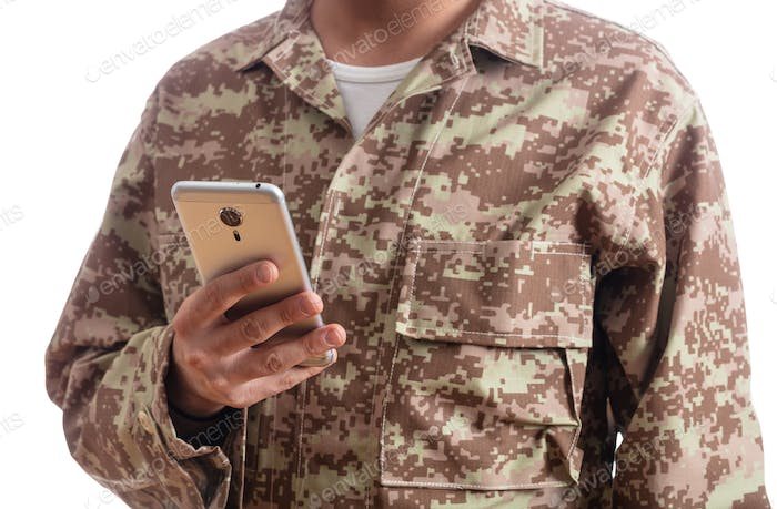 Young soldier holding a mobile phone standing on white background