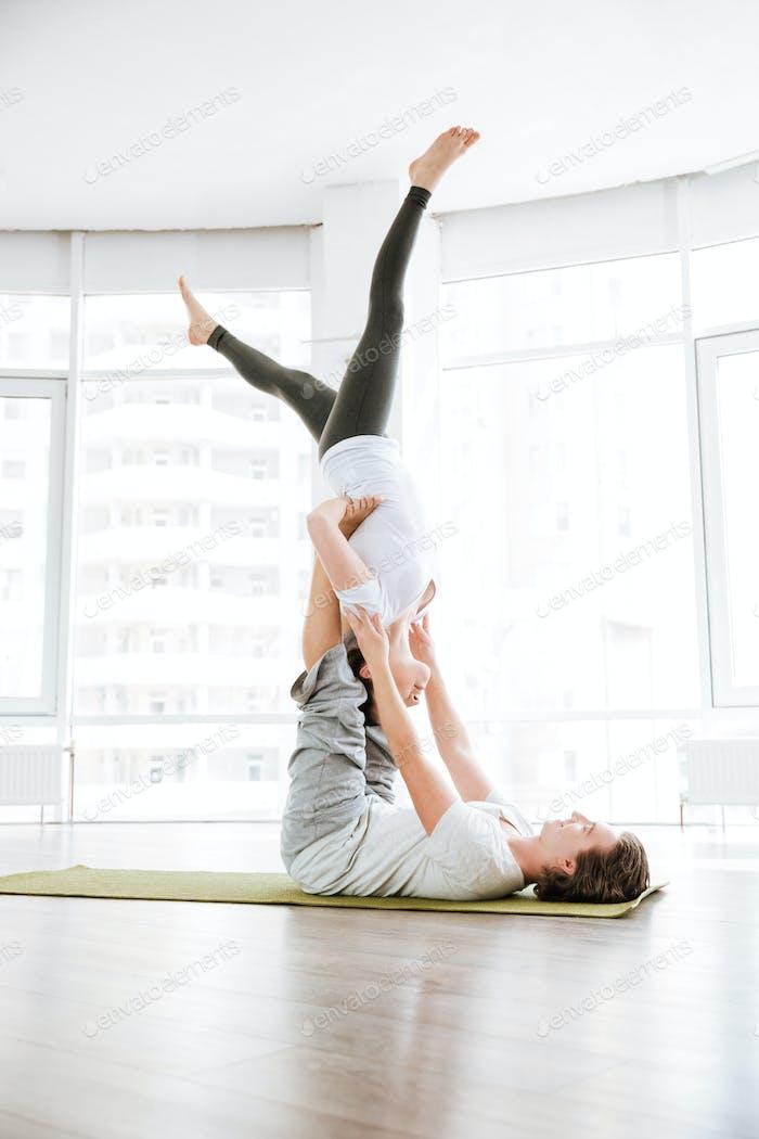Couple doing acro yoga exercises in studio together