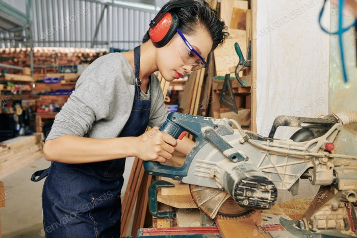 Woodworker cutting plank