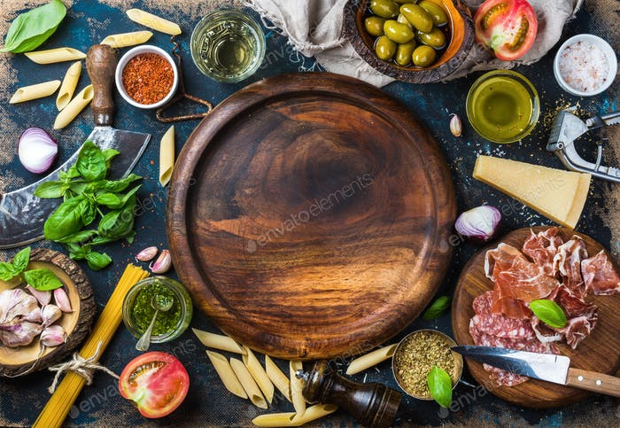 Italian food cooking ingredients on dark plywood background, copy space