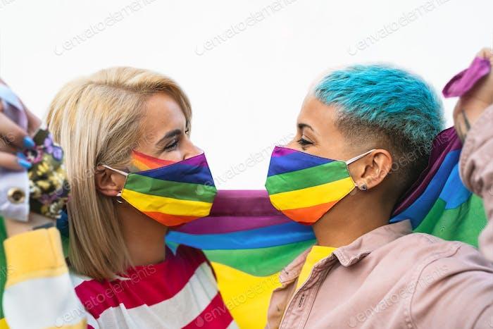Glückliches schwules Paar mit Gesichtsmaske, das Gay Pride Event während der Coronavirus-Pandemie feiert