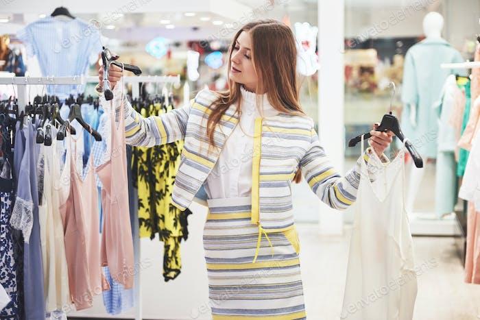 Frau, die Kleidung einkaufen. Shopper Blick auf Kleidung drinnen im Laden. Schöne glückliche Lächeln