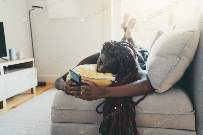 Black girl on a sofa using cellhpone