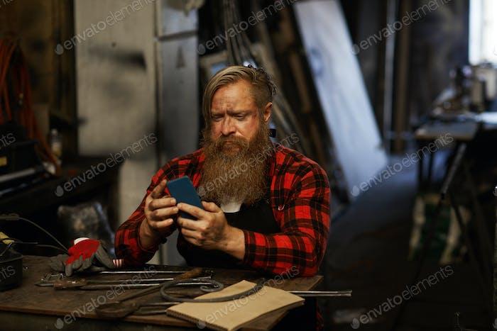 Frowning bearded blacksmith using smartphone