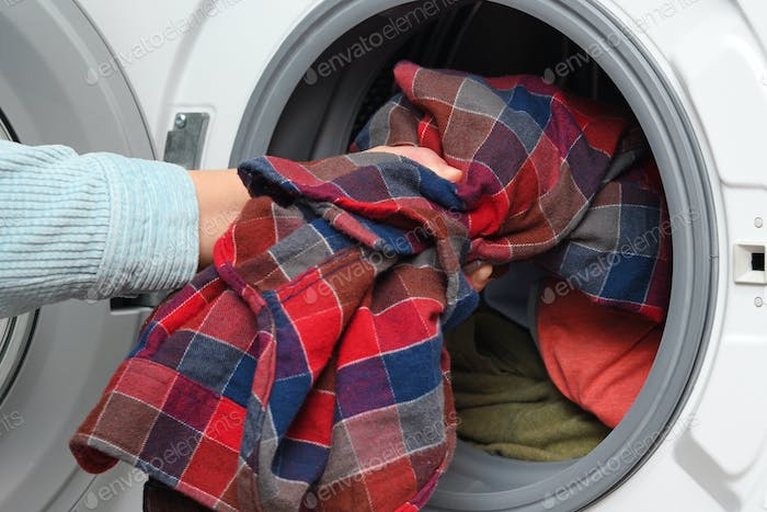 Woman puts clothes in washing machine