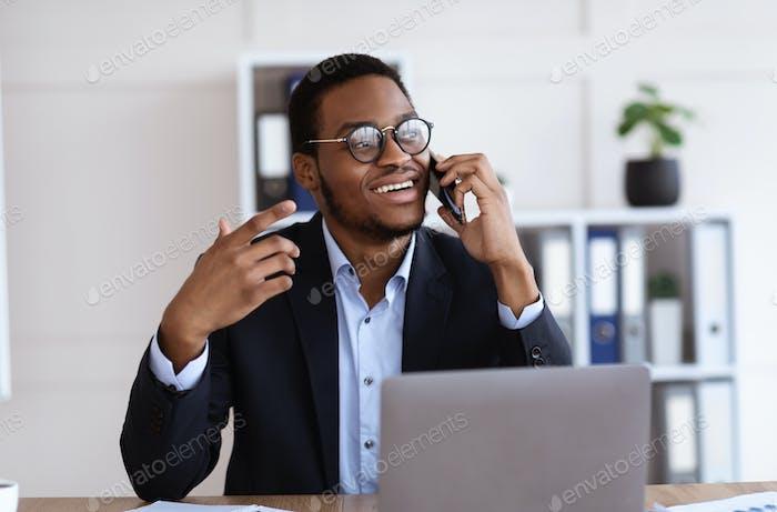 Feliz Empresario africano hablando por teléfono móvil en la oficina