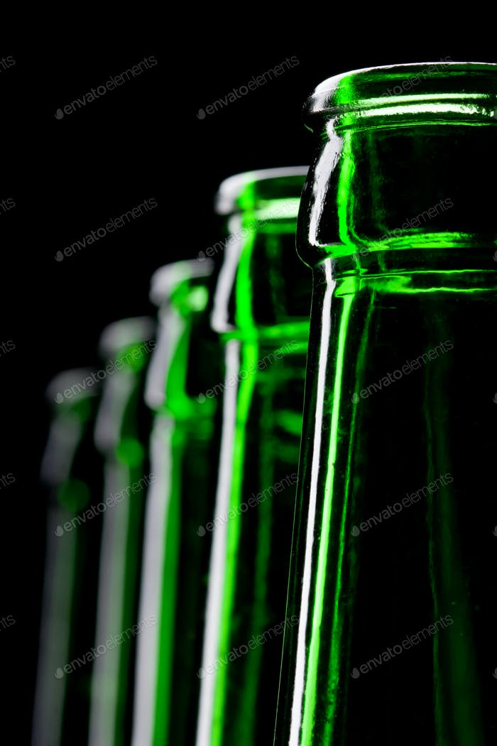 Row of open green beer bottles