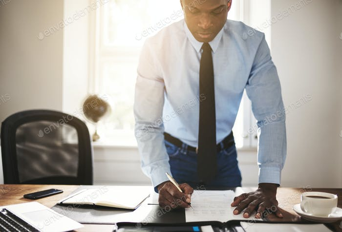 Young businessman signing paperwork at his office desk