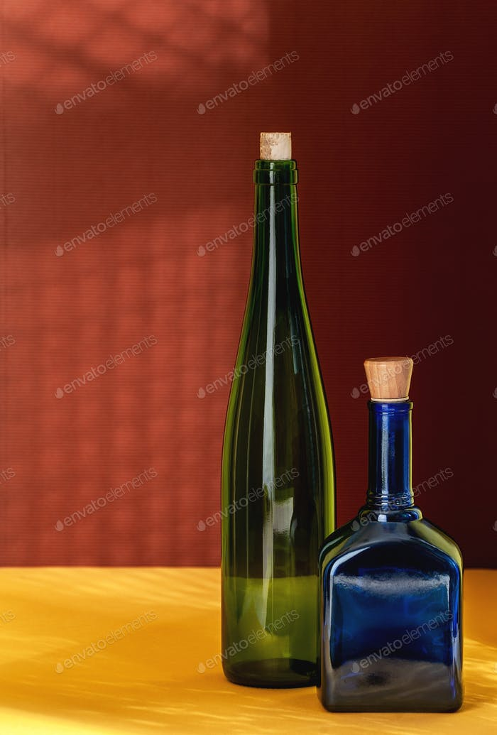 Two colored bottles on a yellow-red textural background. Art sti