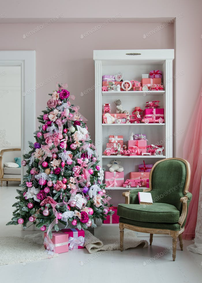 Interior room decorated in Christmas style. No people. An empty green chair. Pink colors. Home
