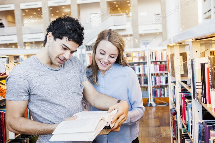 Smiling young friends reading book together in library
