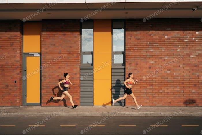 Frauen sprinten morgens draußen.