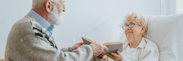 Grey elderly man hands a book to a senior friend lying on a hospital bed