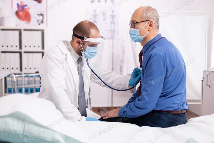Doctor listening elderly patient heart using stethoscope