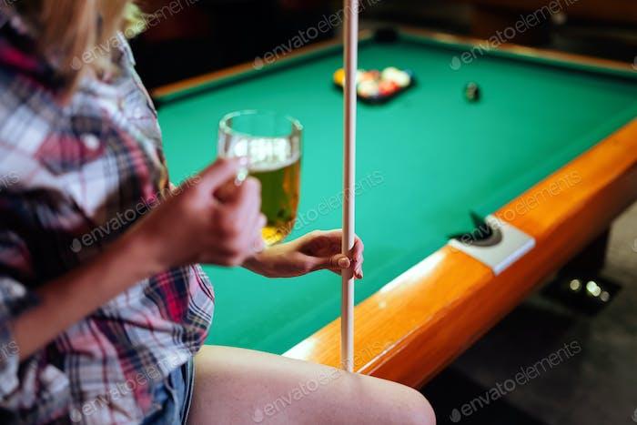 Young smiling girl playing billiard in club