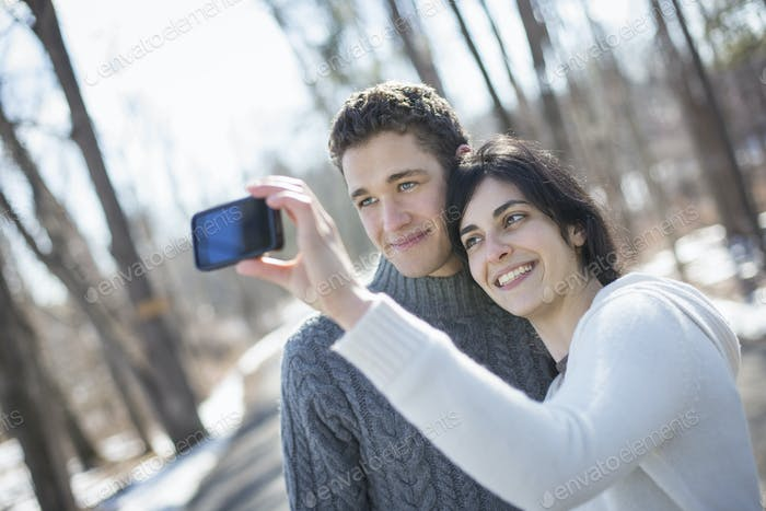 A couple outdoors on a snowy day. Woman holding a camera phone, taking photographs at arms length.