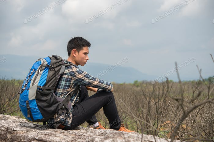 Young hipster Hiker with backpack sitting on top of the mountain.