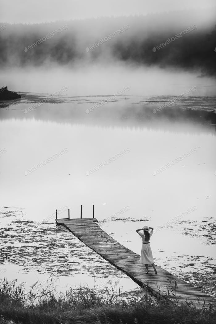 Black and white monochrome picture of young woman in white dress standing alone on footbridge and