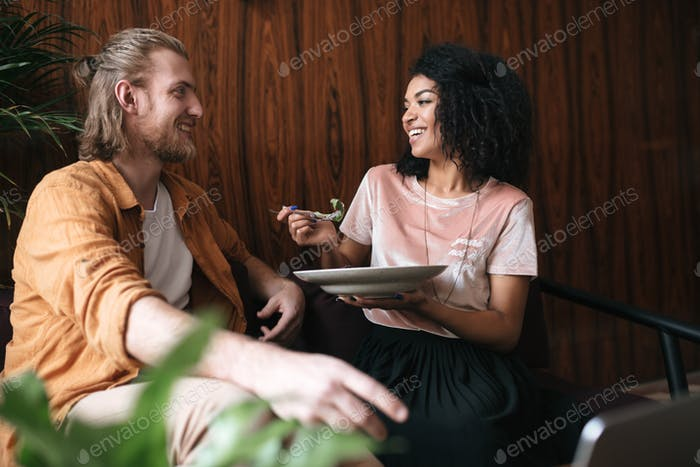 Beautiful young couple sitting and happily talking in restaurant