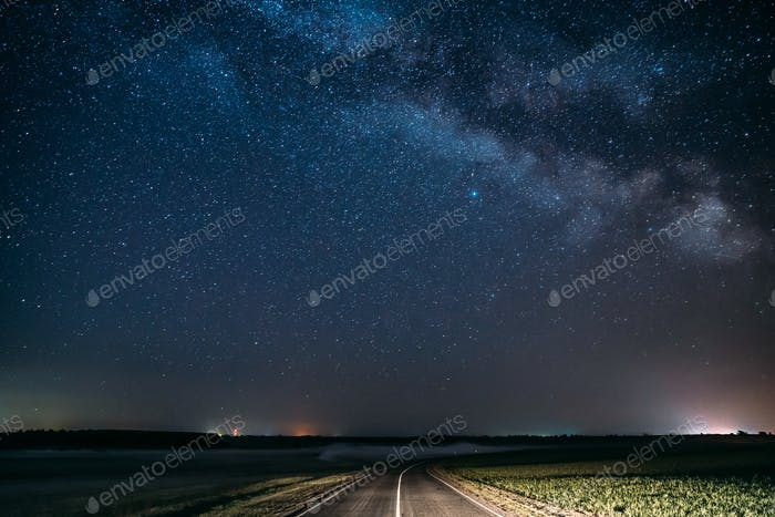 Blue Night Starry Sky Above Country Asphalt Road In Countryside