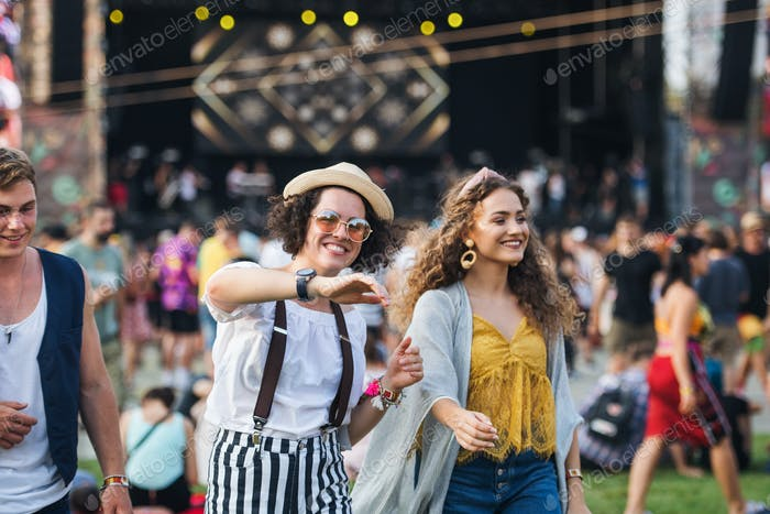 Front view portrait of group of young friends dancing at summer festival.