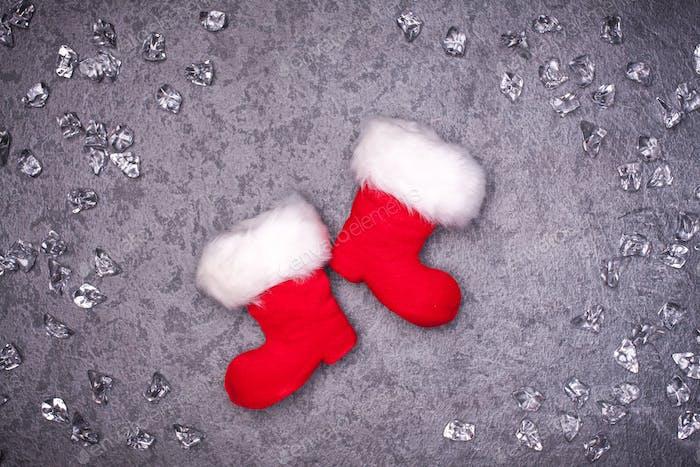 Weihnachts-Grußkarte Noel festlicher Hintergrund. Neujahrssymbol. Santas Schuhe