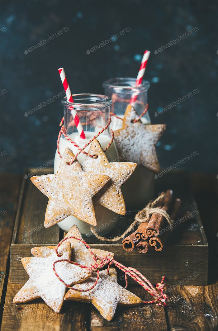 Bottles with milk and Christmas homemade gingerbread star shaped cookies