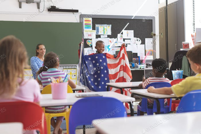 Schoolboy holding american flag in classroom at school