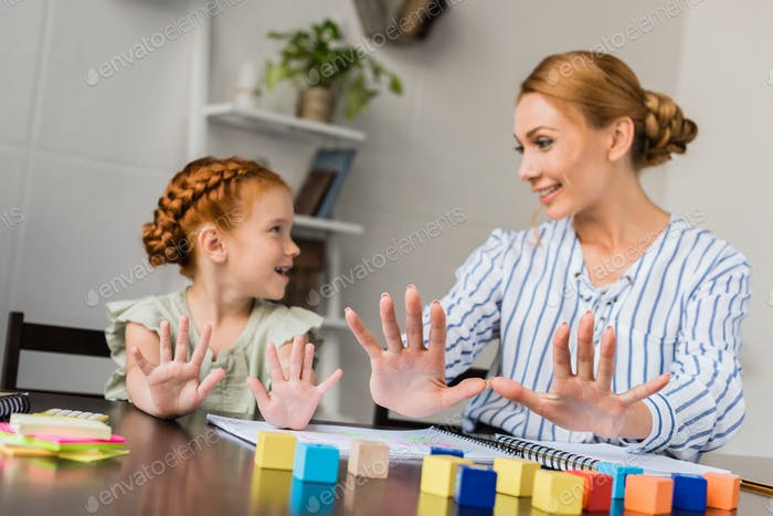happy mother and daughter learning math with fingers at home
