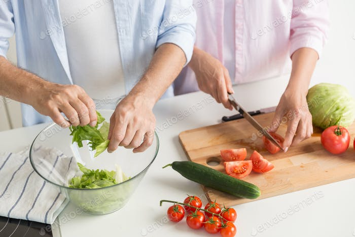 Thumbnail for Cropped picture of mature loving couple family cooking.